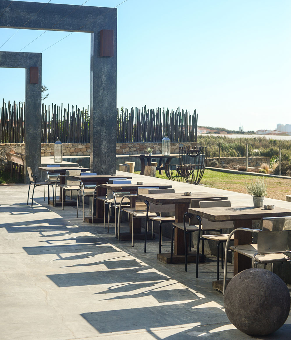 Poolside dining area at Areias Do Seixo Sustainable Hotel in Portugal